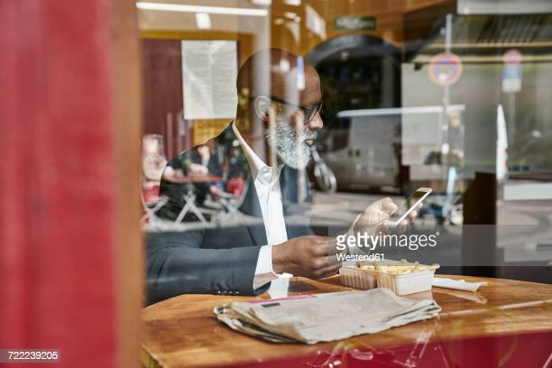 mature businessman sitting in snack bar, eating french fries - fries stock-fotos und bilder