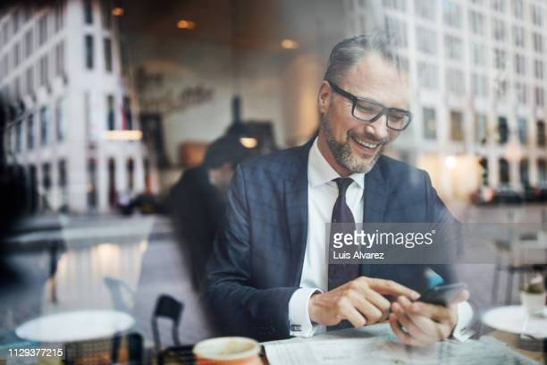 mature businessman sitting inside at cafe and using phone - geschäftskleidung stock-fotos und bilder