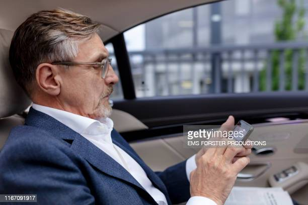 mature businessman sitting on back seat in car and using mobile phone - limousine stock pictures, royalty-free photos & images