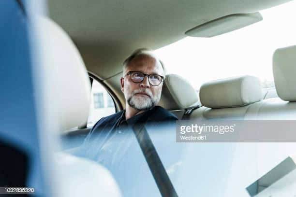 Mature businessman sitting on backseat in car, looking out of window