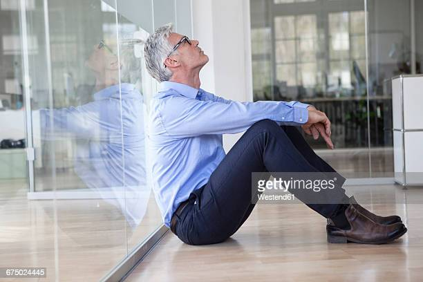 Mature businessman sitting on floor in office