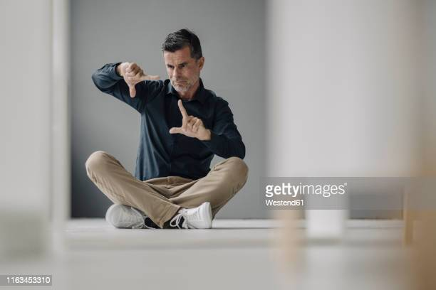 mature businessman sitting on the floor gesturing - 正確 ストックフォトと画像