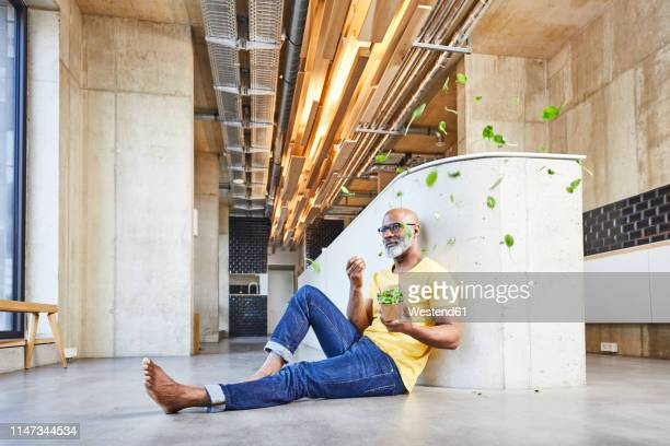 mature businessman sitting on the floor in modern office surrounded by floating lettuce leaves - sitting on ground stock pictures, royalty-free photos & images