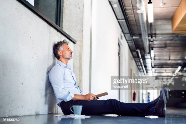 Mature businessman sitting on the floor leaning against the wall