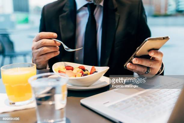Mature businessman sitting outdoors, eating breakfast, using smartphone, laptop on table, mid section