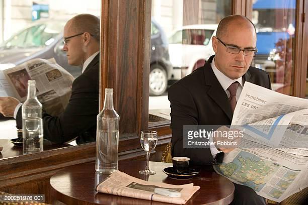 Mature Homme d'affaires, assis à l'extérieur d'un café en lisant le journal