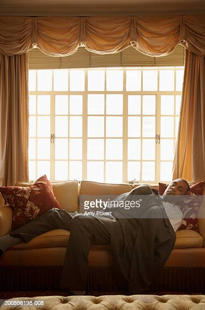 Mature businessman sleeping on sofa, covered with jacket