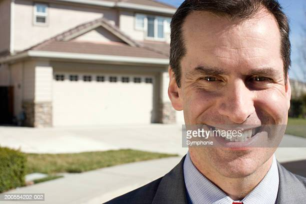 Mature businessman smiling, house in background, portrait