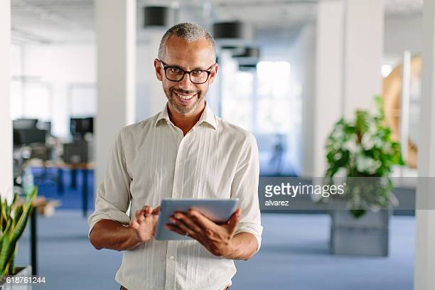 Mature businessman smiling with digital tablet in office