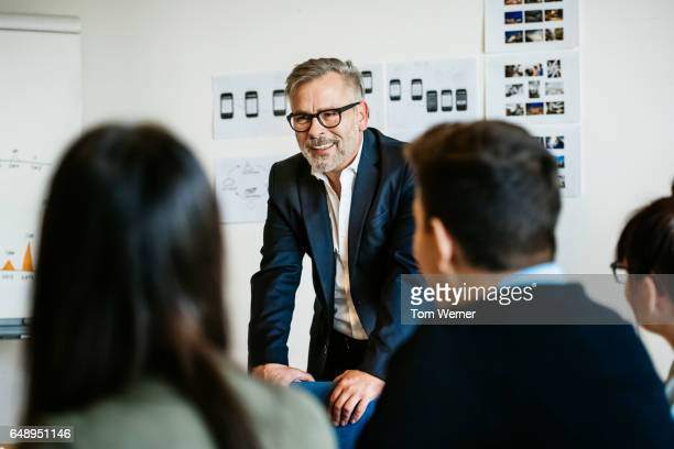 mature businessman speaking in an informal meeting - chef stock-fotos und bilder