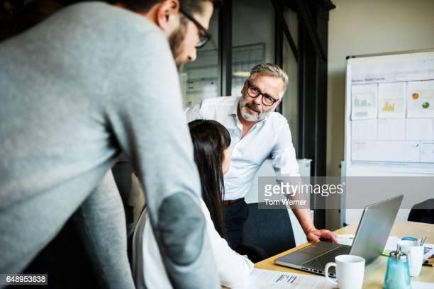 mature businessman speaking in an informal meeting - geschäftsbesprechung stock-fotos und bilder