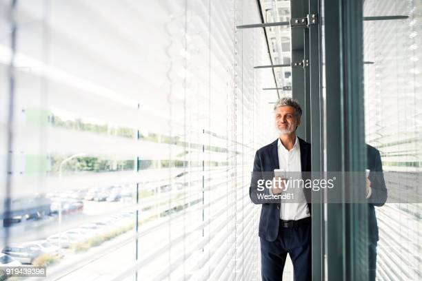 mature businessman standing at outside sunblind holding cell phone - geschäftskleidung stock-fotos und bilder