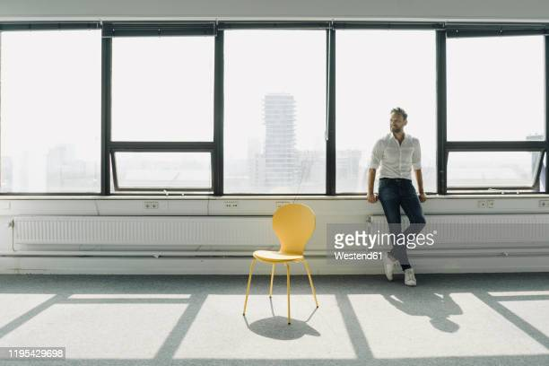 mature businessman standing at the window in empty office - gründer stock-fotos und bilder
