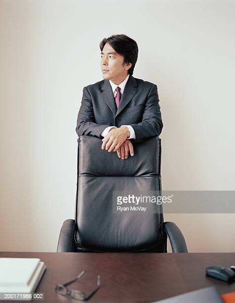 Mature businessman standing behind chair in office, looking away