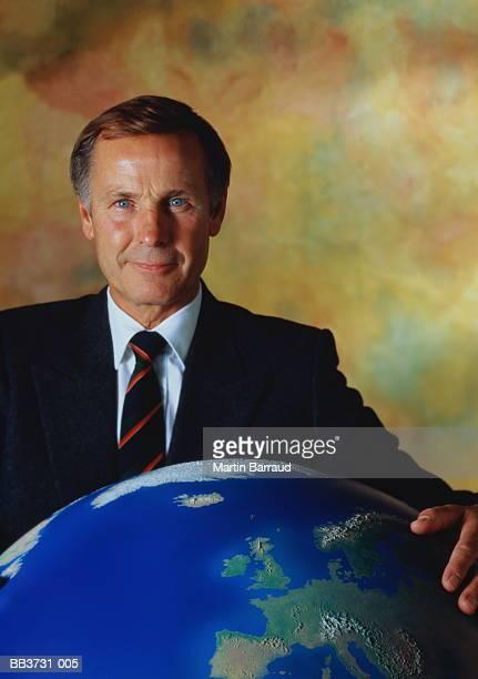 Mature businessman standing behind large globe showing Europe