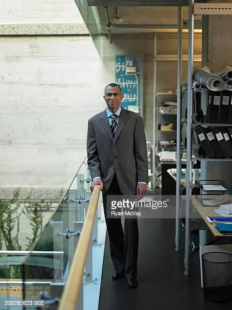 Mature businessman standing beside railing in office, portrait