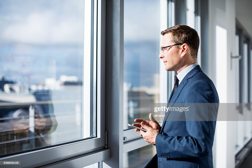 Mature businessman standing by window in office : Stock Photo