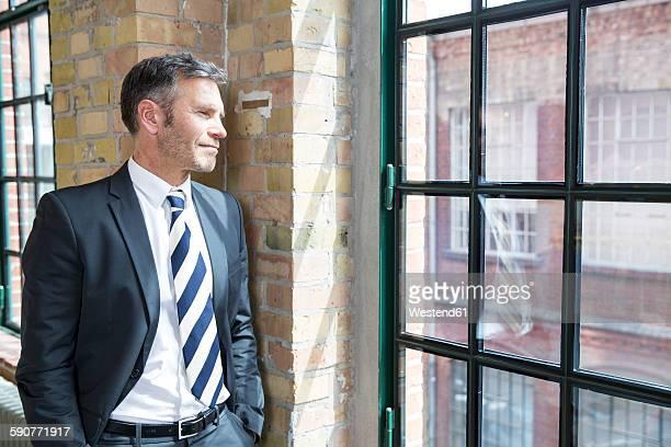 Mature businessman standing by window