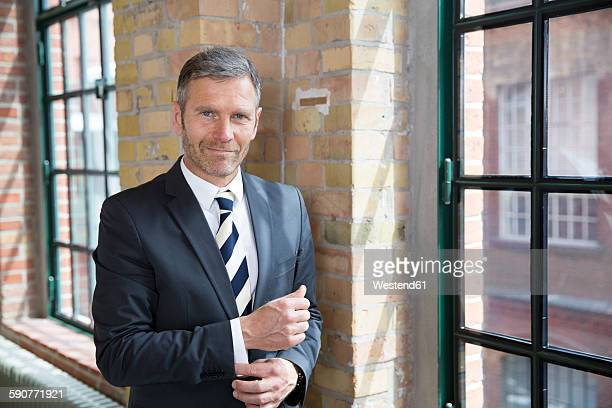 mature businessman standing by window - custom tailored suit stock pictures, royalty-free photos & images