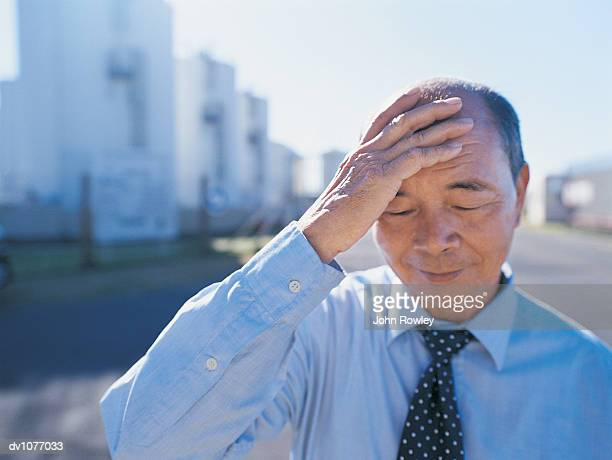 Mature Businessman Standing in an Industrial Park With His Hand on His Head and His Eyes Closed