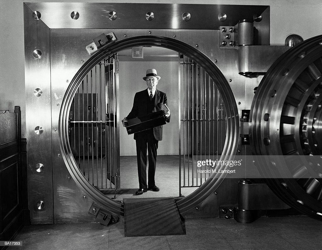 mature businessman standing in bank vault holding briefcase stock