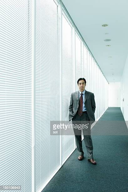 Mature businessman standing in office hallway