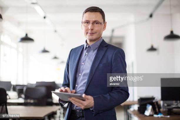 reife geschäftsmann im büro stehen - einzelner mann über 40 stock-fotos und bilder