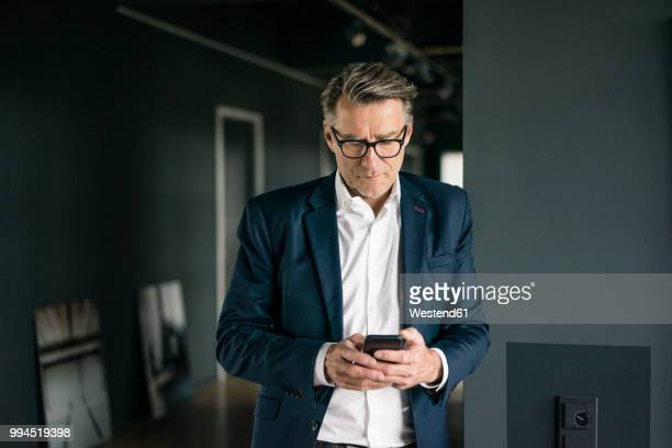 mature businessman standing in office using cell phone - geschäftsmann stock-fotos und bilder