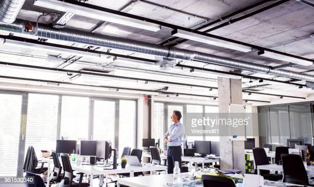 Mature businessman standing in open plan office