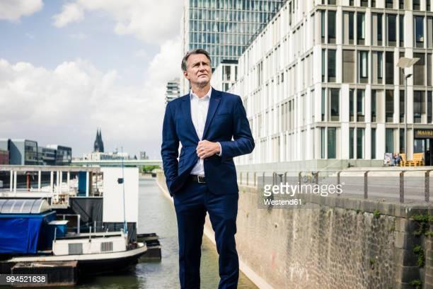 mature businessman standing in the city looking sideways - köln stock-fotos und bilder