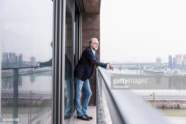 mature businessman standing on balcony - grey blazer stock pictures, royalty-free photos & images
