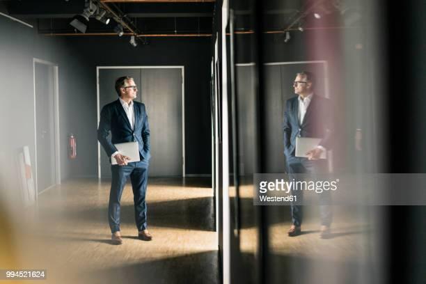 mature businessman standing on office floor holding laptop - weerkaatsing stockfoto's en -beelden