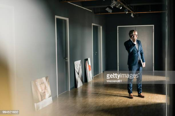 mature businessman standing on office floor with paintings using cell phone - kunsthändler stock-fotos und bilder