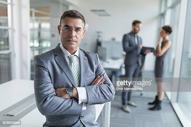 Mature businessman standing with arms crossed in the office.