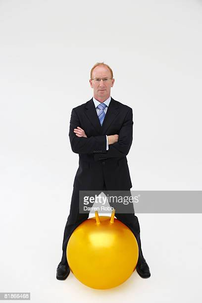Mature businessman standing with gold coloured space hopper