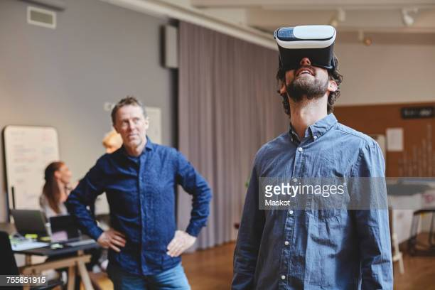 Mature businessman standing with hands on hip while looking at male colleague using virtual reality simulator in creativ