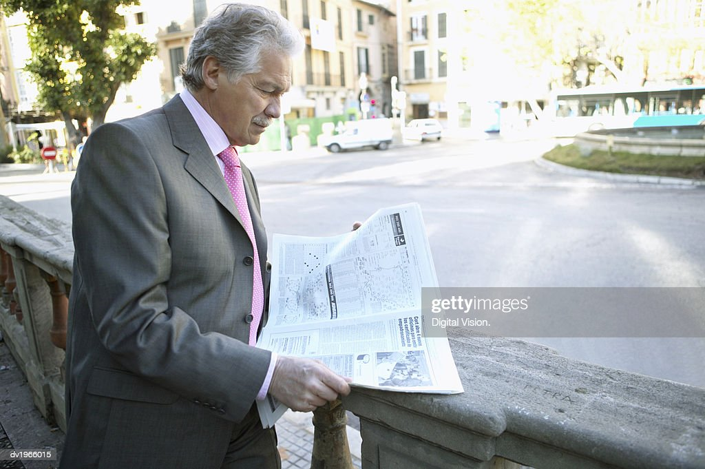 Mature Businessman Stands by a Road Reading a Newspaper : Stock Photo