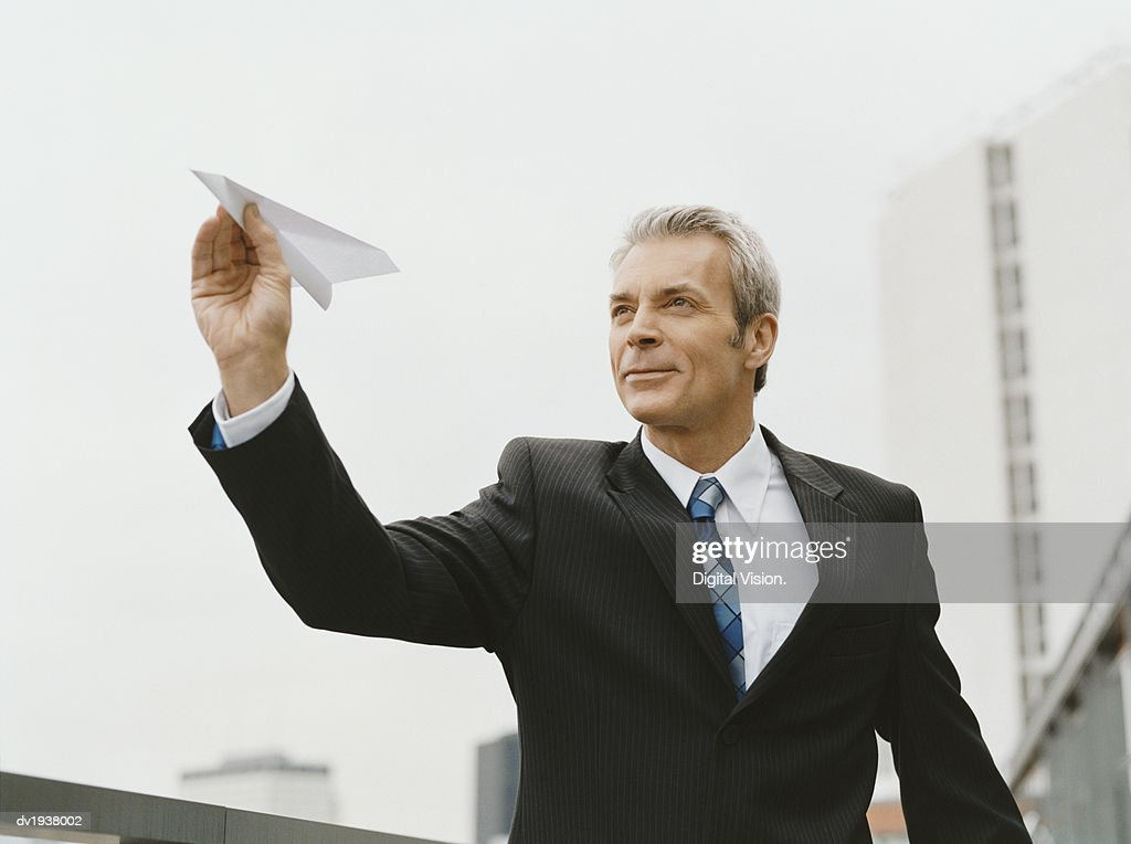 Mature Businessman Stands Outdoors Aiming a Paper Airplane : Stock Photo