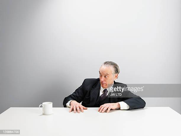 Mature businessman staring at coffee cup on desk