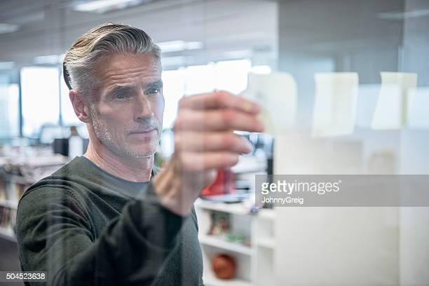 empresário maduro manter observações sobre a expressão séria de vidro, - só um homem maduro - fotografias e filmes do acervo