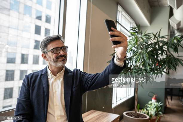 mature businessman taking a selfie at office - following moving activity stock pictures, royalty-free photos & images