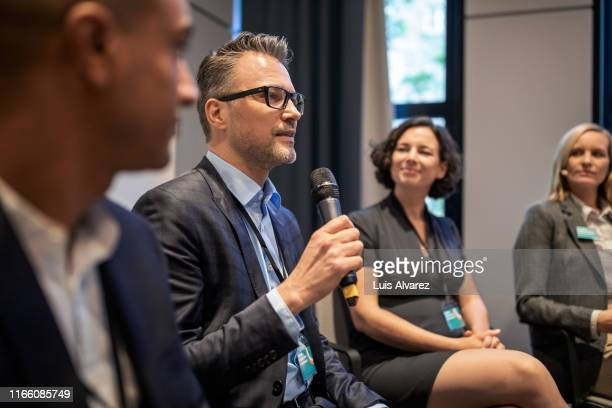 mature businessman talking in a seminar - podiumsdiskussion stock-fotos und bilder