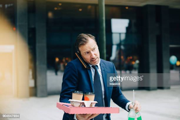 Mature businessman talking on mobile phone while carrying food and drinks in city