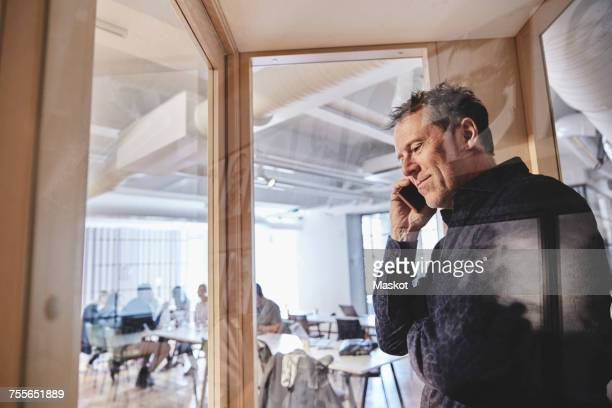 mature businessman talking on smart phone seen from glass at office - telephone booth stock pictures, royalty-free photos & images