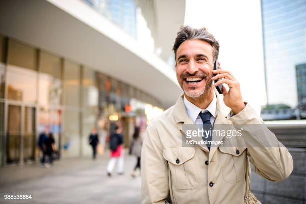 mature businessman talking on the phone. - grey suit stock pictures, royalty-free photos & images