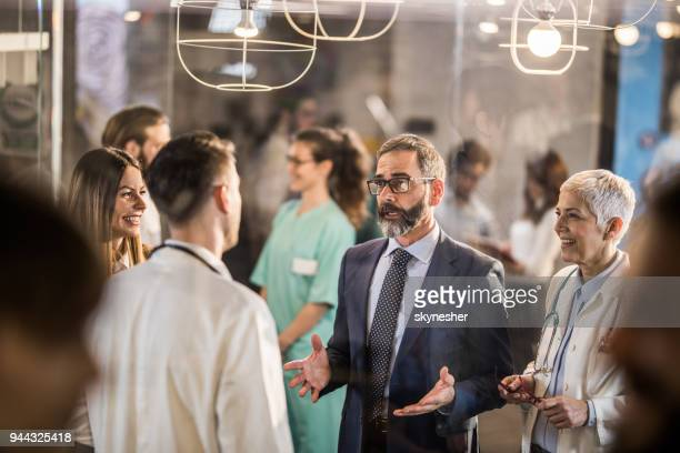Mature businessman talking to doctors in a hospital hallway.