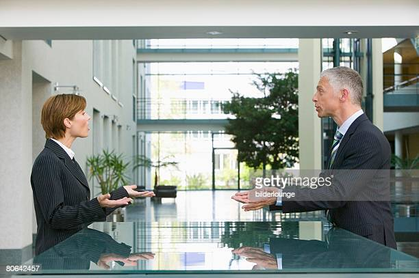 mature businessman talking to female employee at reception