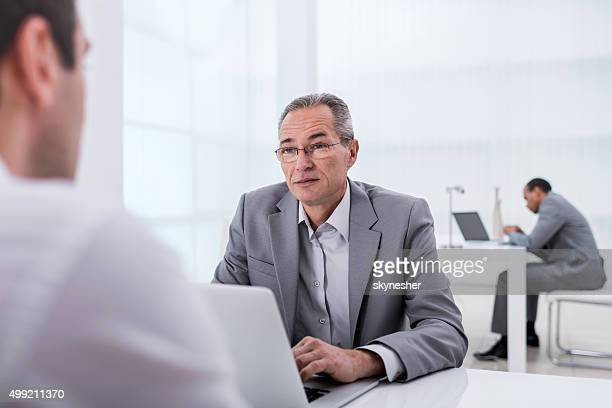 Mature businessman talking to his colleague on a business meeting.