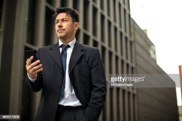 mature businessman text messaging. - transportation building type of building stock photos and pictures