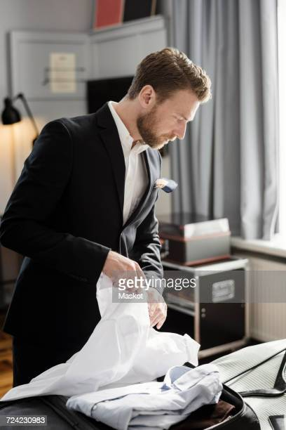 Mature businessman unpacking luggage on bed in hotel room